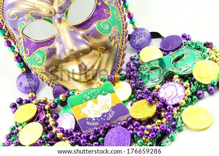 Mardi Gras mask with beads and doubloons at an angle. - stock photo