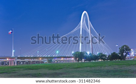 Margaret Hunt Hill Bridge and US flags at night in Dallas, Texas from Trinity Park - stock photo