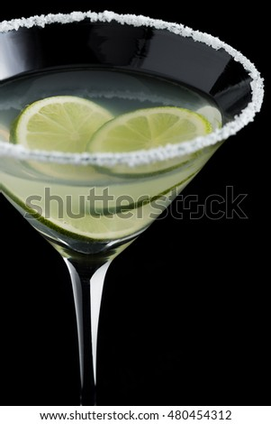 Margarita cocktail with lime on black background