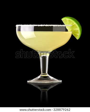 Margarita cocktail with lime wedge and salty rim on black background - stock photo