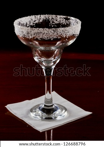 margarita glass decorated with a salt rim, served on a dark bar fading into black - stock photo
