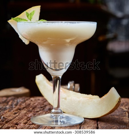 margarita melon cocktail with copy space on wooden background.  - stock photo