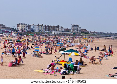 MARGATE, UK-JULY 14: Visitors flock to Margate's beach during the unusual heatwave in Britain.Margates Main sands have been awarded a blue flag for high standards. July 14, 2013 Margate, Kent UK - stock photo