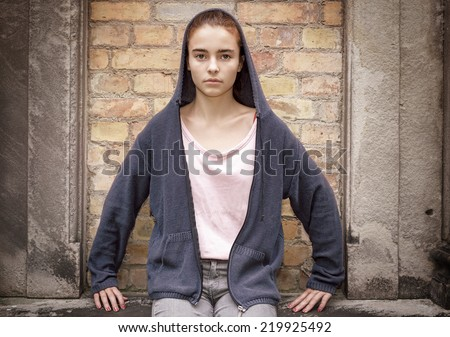 maria like portrait of a sitting teenager girl in front of an old wall - stock photo