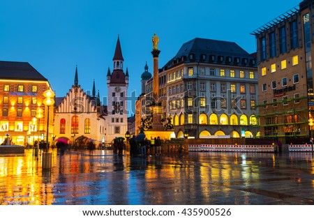 Marienplatz at night in Munich, Germany with old town hall and other buildings - cafes, bars, shops and restaurants. Motion blurred people. - stock photo