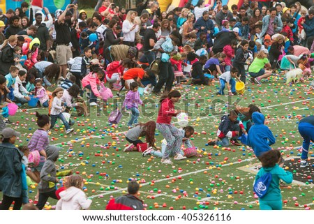 MARIETTA, GA - MARCH 26:  Kids and parents eagerly dash out onto the football field at the start of a massive community Easter egg hunt at a local high school on March 26, 2016 in Marietta, GA.