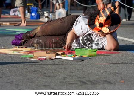 MARIETTA, GA - OCTOBER 11:  A chalk artist creates an elaborate Halloween scene on a downtown street as part of the Marietta Chalkfest on October 11, 2014 in Marietta, GA.  - stock photo