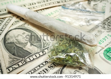 Marijuana cigarette and dry cannabis in sack on dollar banknotes. - stock photo