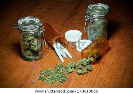 Marijuana On Table. Marijuana on a wood table. In piles, jars, prescription bottles and rolled into joints. - stock photo