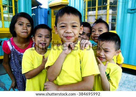 MARIKINA CITY, PHILIPPINES - FEBRUARY 12, 2016: Young boys and girls huddle and smile for the camera at a playground in Marikina City, Philippines - stock photo