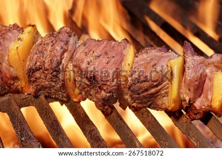 Marinated BBQ Meat Or Beef Kebab Kabob On Hot Grill. Flames of Fire on The Background. Summer Party or Picnic Food. - stock photo