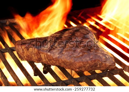Marinated Beef Steak On The Hot BBQ Charcoal Grill. Flame Of Fire In The Background. - stock photo