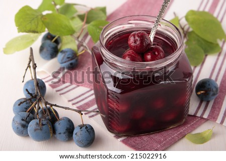 Marinated berries of blackthorn in a square glass jar - stock photo