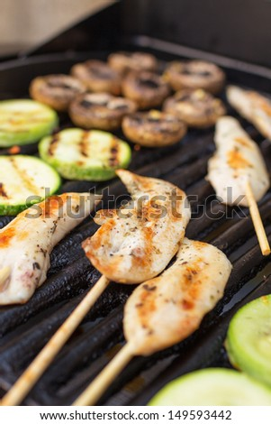 Marinated chicken fillets with vegetables on barbecue grill - stock photo