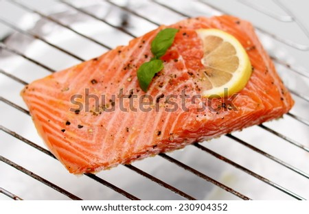 Marinated salmon fillet with lemon on grill, soft focus - stock photo