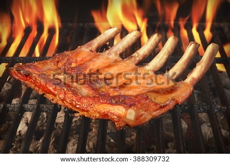 Marinated With BBQ Sauce Pork Baby Back Or Spare Rib On The Hot Charcoal Grill With Bright Flames In The Background, Close Up - stock photo