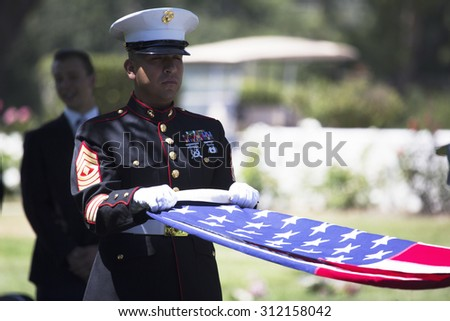 """Marine folds flag at Memorial Service for fallen US Soldier, PFC Zach Suarez, """"Honor Mission"""" on Highway 23, drive to Memorial Service, Westlake Village, California, USA, 06.19.2014 - stock photo"""