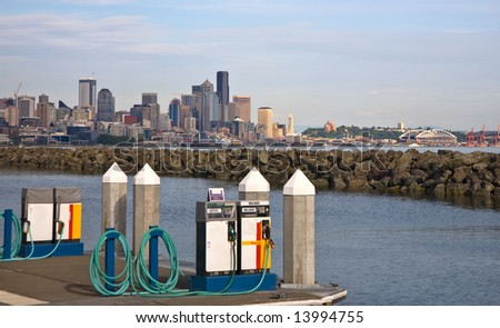 Marine fuel pumps at marina, city skyline in the distance - stock photo