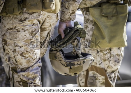 Marine helmet held by the soldier. - stock photo