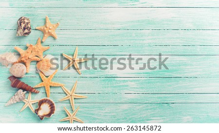 Marine items on turquoise painted wooden background. Sea objects - shells, sea stars on wooden planks. Selective focus. Toned image.  - stock photo
