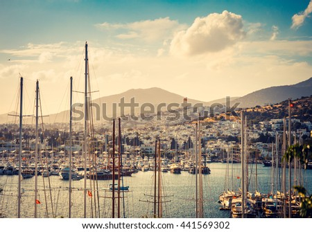 Marine landscape with yachts in a Bodrum harbor. Seaside view with sailboats and mountains at sunset. Bodrum marina with yachting and luxury leisure. Travel and sea vacation in Turkish Riviera. - stock photo