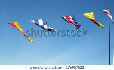 Marine signal flags waving in the background of the sky