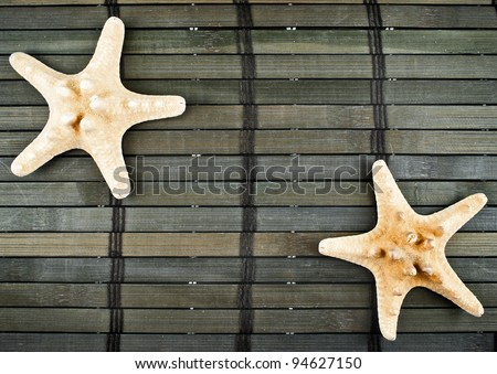 Marine still life of two yellow sea-stars on a wooden mat in dark tones.
