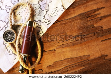 Marine still life spyglass and world map on wooden background - stock photo