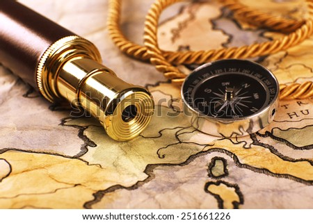 Marine still life with world map and spyglass on wooden table background - stock photo