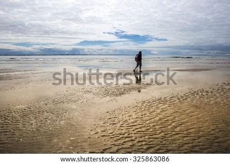 maritime seaside landscape with man walking on the sand, garonne estuary near Royan, France - stock photo