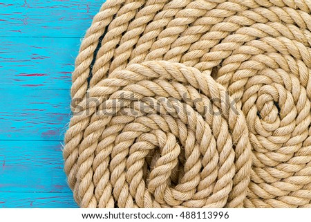 Maritime theme background of wound up rope over worn out blue painted surface with copy space