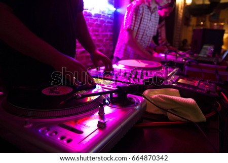 MARIUPOL,UKRAINE-12 JULY,2013: Black man play dj set on party in bar.Disc jockey mixing music tracks on hip hop party.Bright magenta lighting background.Night club party.Dj scratching vinyl records