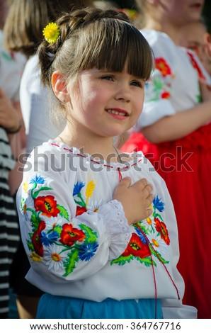 Mariupol, Ukraine - May, 21 2015. National Vyshyvanka Day.  Nice small  girl wearing vyshyvanka sings the Hymn of Ukraine and hold hand on her heart. - stock photo