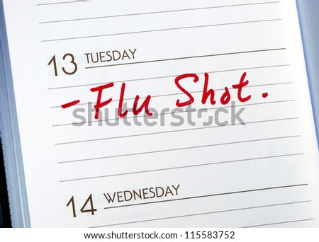 Mark the date on the day planner to have a flu shot - stock photo