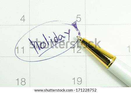 Marked and written holiday in a calendar. - stock photo