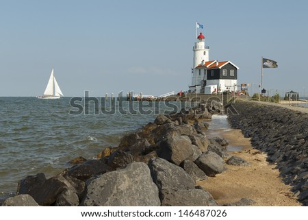 "MARKEN - JULY 15: A sailboat sails past the ""Paard van Marken"" lighthouse in Marken, the Netherlands, on July 15, 2013. - stock photo"