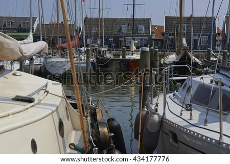 Marken, The Netherlands - June 6, 2013: A typical wooden houses and boats in the harbor  on the former isle of Marken in the Netherlands.