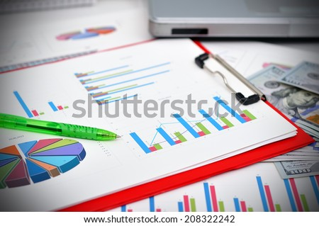 market analysis concept with financial data, pen, laptop and calculator