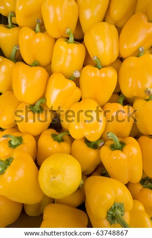 Market arrangement of polished yellow peppers with one lemon.