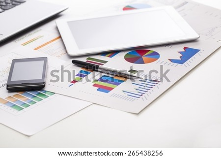 Market. Financial charts on the table with tablet  phone and pen - stock photo