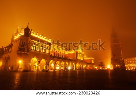 Market hall and town city hall at main Cracow square at misty night with golden sky - stock photo