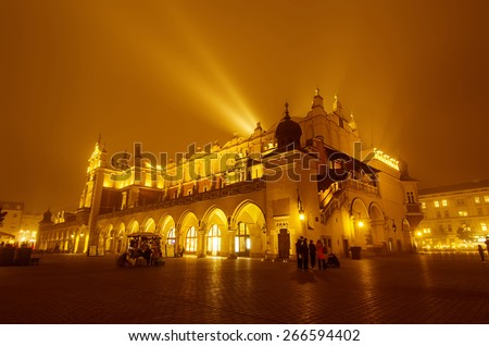 Market hall at main Cracow square at misty night with golden sky - stock photo
