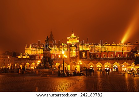 Market hall at main Cracow square at misty night with golden sky and  Adam Mickiewicz monument - stock photo