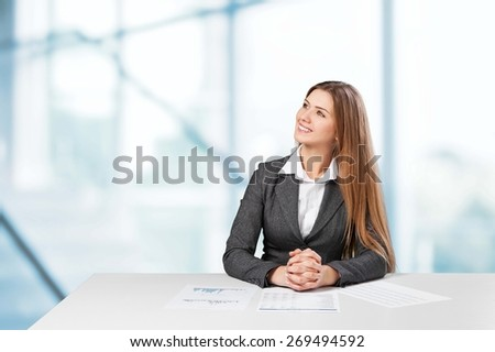 Market. Pretty young businesswoman sitting at desk with business scheme and icons - stock photo