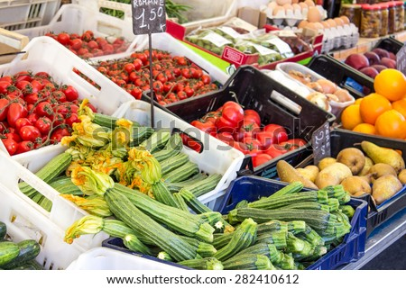 Market stall with tomatoes, zucchini, zucchini flowers, onions, eggs, apples, pears and oranges / market stall / fruits and vegetables