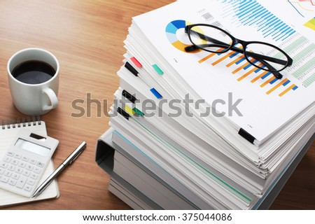 Marketing data analysis. Wooden table. Wooden office desk with pile of documents, calculator and coffee mug.  - stock photo