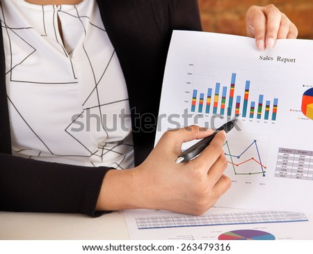 Marketing executive making a business presentation and analyzing sales report with charts and graphs - stock photo