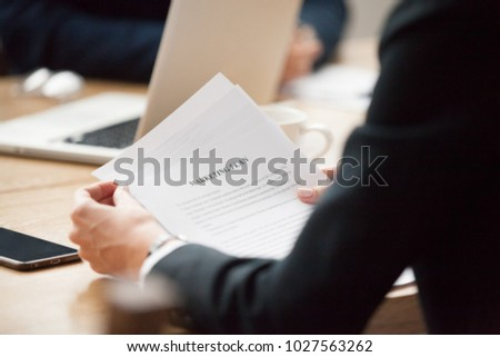 Marketing plan analysis concept, businesswoman reading document with strategy for corporate campaign, sales person or executive manager analyzing new improvement ideas, close up over shoulder view