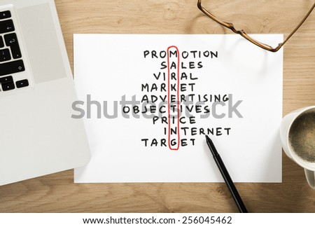 marketing strategy plan crossword puzzle on the office desk - stock photo