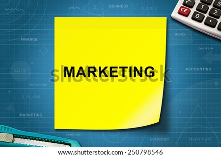 marketing text on yellow note with graph paper - stock photo